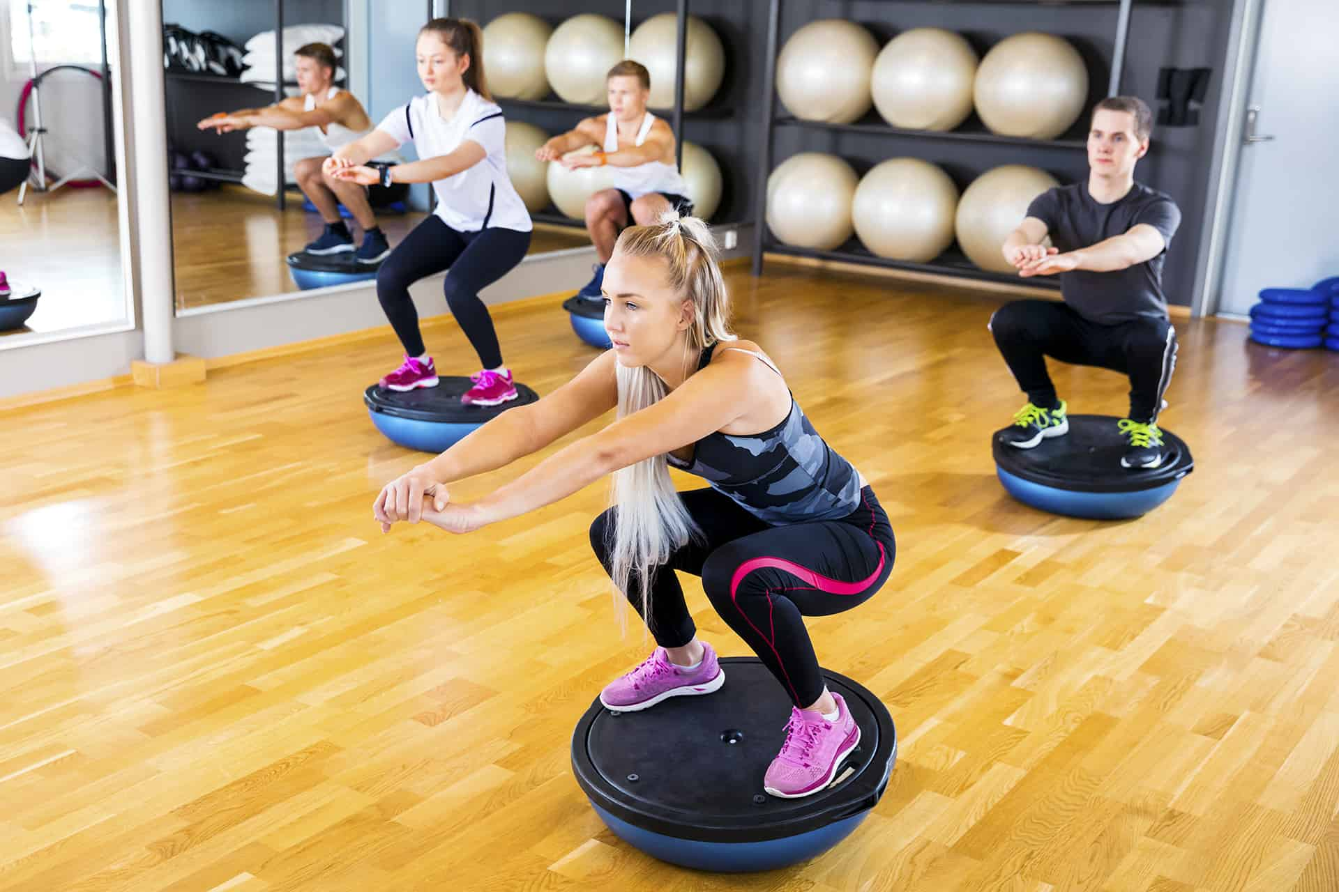 Focused group training squats on half ball at fitness gym
